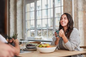 Frau beim Kaffee trinken in Küche