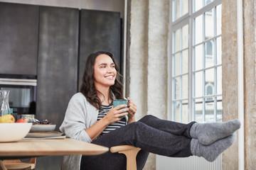 Kurvige Frau sitzt gemütlich in Küche mit Kaffee