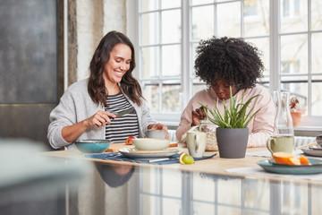 Zwei kurvige Frauen essen Frühstück in Küche