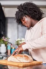Afrikanische Frau beim Brot schneiden in Küche
