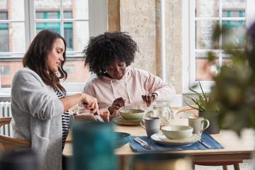 Zwei Frauen essen Müsli zum Frühstück in Küche