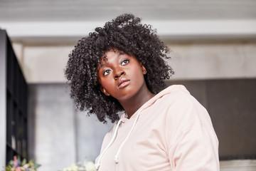 Afrikanische junge Frau mit Afro schaut neutral