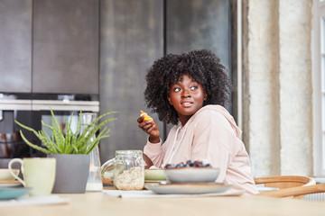 Afrikanische junge Frau beim Frühstück essen