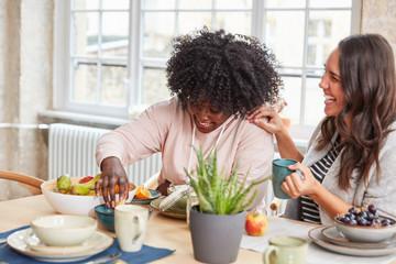 Zwei Freundinnen lachen beim Frühstück essen