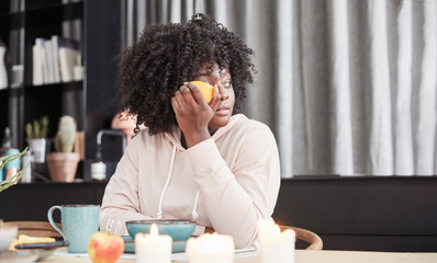 Afrikanische Frau mit Apfel in Küche
