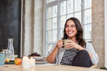 Frau lacht beim Kaffee trinken in Küche