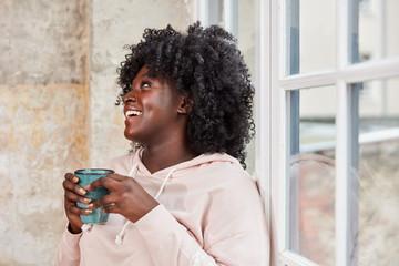 Lachende afrikanische Frau mit Tasse Kaffee