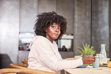 Junge afrikanische Frau sitzt am Tisch in Küche