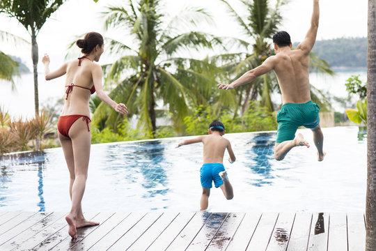 Happy young family jumping into swimming pool