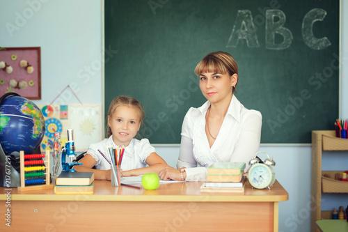 Teacher And Her Students In Classroom Teacher Helping Schoolgirl With Her Homework In Classroom At