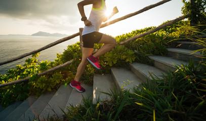 Fototapeta Determined woman running up on seaside mountain stairs obraz