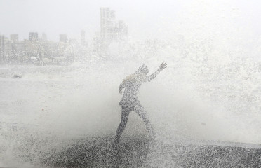 A man loses his balance as he gets drenched by a large wave during high tide at a seafront in Mumbai