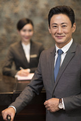Cheerful businessman at hotel reception