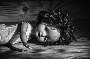 Old broken doll on a wooden table.