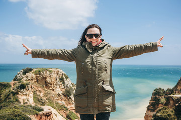 Young beautiful girl smiles and shows positive emotions and is happy on the Atlantic coast in Portugal.