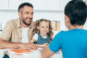 smiling father and kids doing homework together at home Fotoväggar