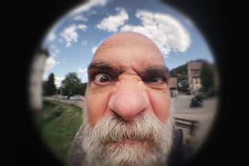 an angry man looking to a peephole door