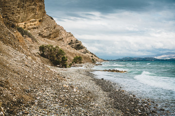 Crete, Greece. beach with rocks and cliffs with view towards sea ovean on a sunny day.