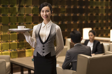 Cheerful young waitress serving coffee