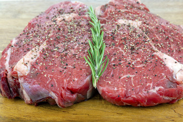 Peppered Raw Rib Eye Steaks on a Wooden Board