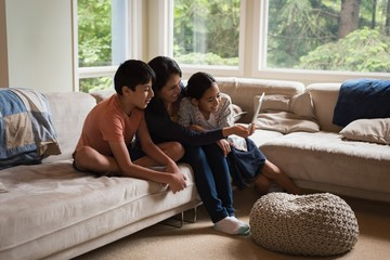 Mother and kids having video call on laptop in living room