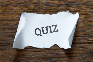 Quiz - an inscription on a piece of white paper, a scroll. The concept of interesting questions, intellectual leisure, family pastime.