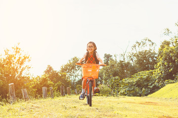 A little cute girl with glasses riding on bicycle in summer park