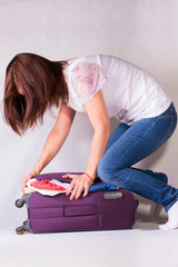 The girl packing crammed suitcase
