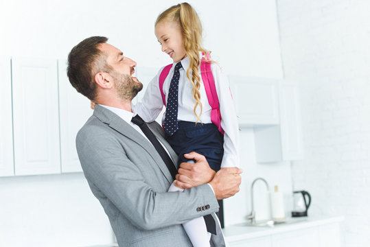 portrait of happy father in suit holding daughter in school uniform with backpack on hands in kitchen, back to school concept