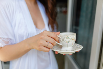 White mug with a pattern with hot coffee inside the in the hands of women in Bathrobe standing on the balcony of her bedroom. Woman wearing white bathrobe with cup of coffee in her hands. Close up