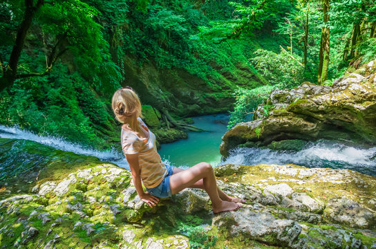 beautiful girl sits on top of a waterfall and admires a beautiful view, Georgia