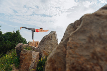 The main asana. Dark-haired yoga teacher showing the main asana while standing on high rock in the forest
