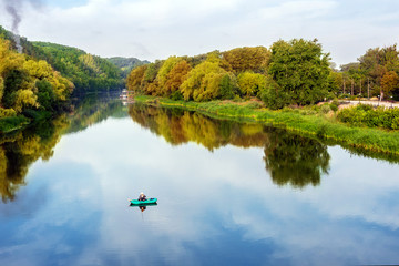 Bright scenic landscape of river in bright multicolored autumn forest with colorful trees. Blue sky reflection mirrored in pond surface.Fisherman fishing in boat at early morning. Aerial top view