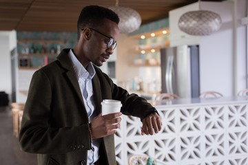 Businessman looking at smartwatch while having coffee in