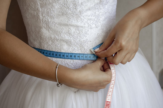 Bride measuring her waist before the wedding day