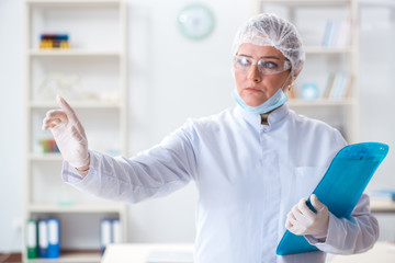 Woman doctor pressing buttons in lab