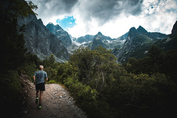 Trail runner run in mountains, sport photo in nature