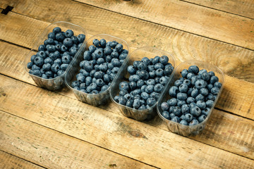 Juicy and blueberries in a container on an old wooden table in the summer