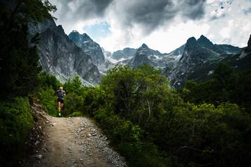 Trail Runner in Mountains, dark sky in background