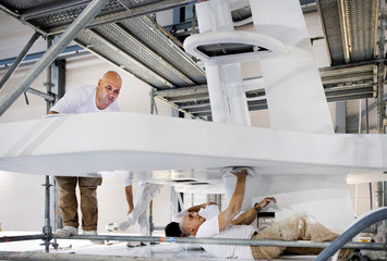 People work on a yacht under construction at the Heesen Yachts shipyard in Oss