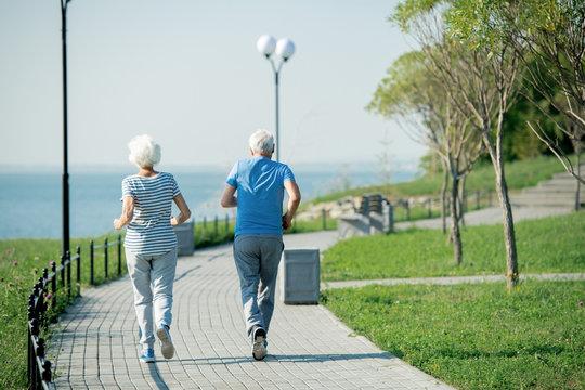 Back view portrait of active senior couple running on park lane along sea shore outdoors , copy space