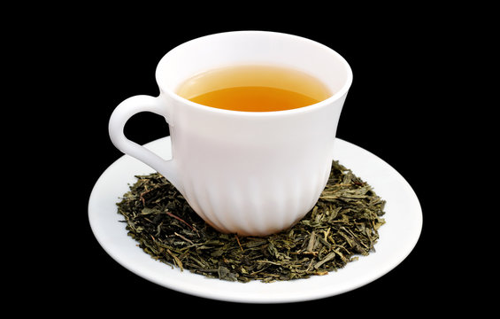 White cup with green tea from close-up isolated in black background. Sencha. Leaves of tea on saucer.