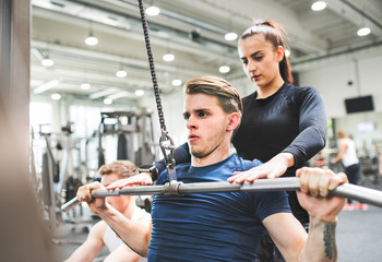 Young man in gym working out on pull-down machine, a personal trainer behind him.