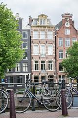 Biciclette in primo piano e palazzi caratteristici di Amsterdam sullo sfondo