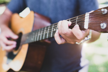Close up of guitarist hand playing guitar. Musical and instrument concept. Outdoors and Leisure theme. Selective focus on left hand.
