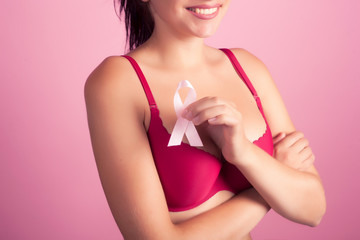 Young woman in rad bra with breast cancer pink awareness ribbon