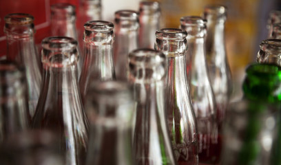 Many used glass bottles arranged in rows for recycling. Opened empty soda bottles background