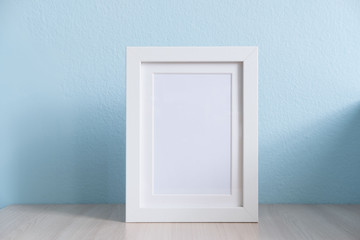 blank white picture frame on the table wood with blue background
