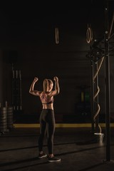 Woman showing her muscle in gym