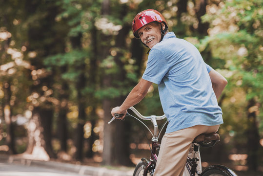 Old Man Riding on Bicycle in Park in Summer .